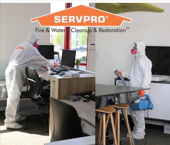 Tech spraying SERVPRO disinfectant and wiping high touch-points