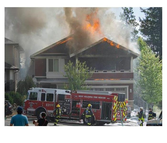 Fire fighters extinguishing a house fire in West Kelowna, BC